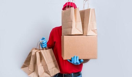 Symbol für Coronakrise im Einzelhandel - Zusteller liefert Ware und versteckt sich dahinter